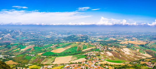Aerial top panoramic view of landscape with valley, green hills, fields and villages of Republic San Marino suburban district with blue sky white clouds background. View from San Marino fortress. Wall mural