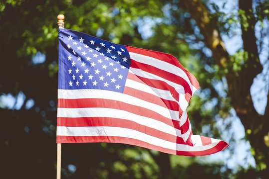 Closeup shot of the united states flag on a pole with a blurred background
