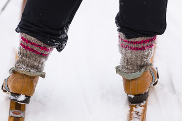 Skier in old leather boots rides wooden skis