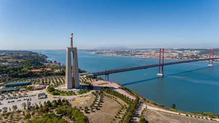 Aerial. Panorama from sky, a 25 de Abril Bridge and a statue of Jesus Christ. Lisbon. Wall mural