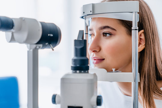 Beautiful young girl checking the eye vision in modern ophthalmology clinic