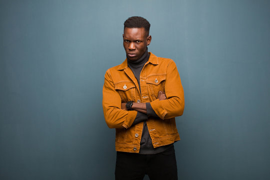 young african american black man feeling displeased and disappointed, looking serious, annoyed and angry with crossed arms against grunge wall