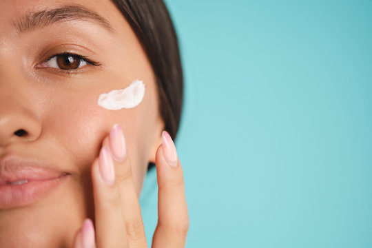 Close up pretty Asian girl applying cream on clean skin over colorful background isolated