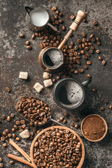 Fototapete - Coffee cup, sugar, milk and coffee beans on dark background.