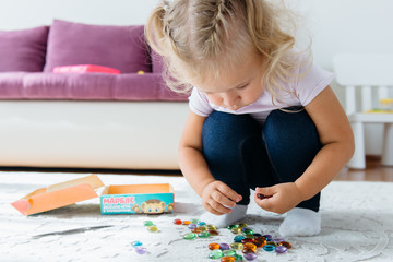 girl playing with colorful stones, learning colors