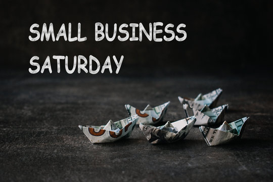 Small business Saturday concept. Many Origami ships from US dollars on dark background with text Small business Saturday.