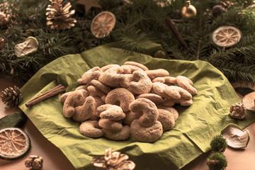leckere weihnachtsplätzchen vor einem Gesteck aus Tannenzweigen