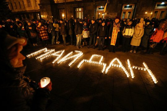 """People gather near lit candles arranged to read """"Maidan"""" during a rally marking the 6th anniversary of the beginning of the Ukrainian pro-European Union (EU) mass demonstrations, in Kiev"""