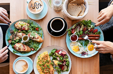 Different colorful meals for breakfast or lunch time on a plate with cutlery on woman's hands. Fried eggs, omelette, bruschetta and sausage on a wooden teble in restaurant. Flat lay top view. Papier Peint