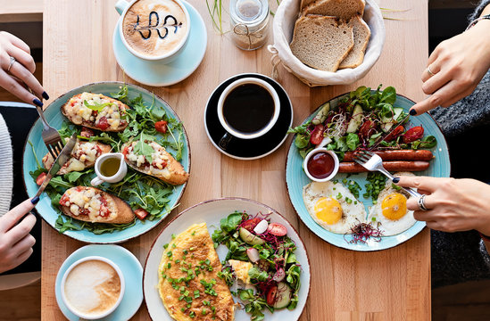 Different colorful meals for breakfast or lunch time on a plate with cutlery on woman's hands. Fried eggs, omelette, bruschetta and sausage on a wooden teble in restaurant. Flat lay top view.
