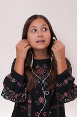 young girl has earphones in her ear, she speaks by phone