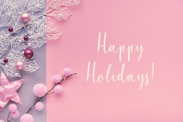 """Romantic Christmas flat lay, top view on two color paper background with lettering bouncy text """"Happy Holidays"""".Trinkets and decorative twigs with frosted geometric leaves and textile baubles."""