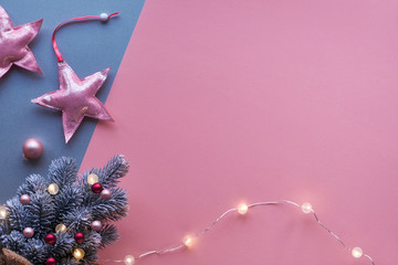 Christmas flat lay, top view on two color pink and silver paper with soft pink metallic textile stars. Small artificial Xmas tree decorated with light garland and magenta trinkets, copy-space.