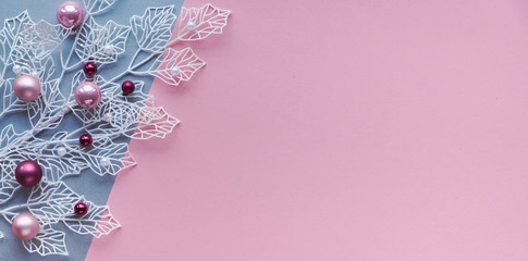 White winter twigs with shiny geometric leaves and scattered glass Xmas trinkets, pink and magenta. Panoramic Christmas flat lay, top view, two color paper, pink and silver, background with copy-space