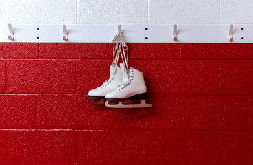 Figure skates hanging in locker room over red background with copy space