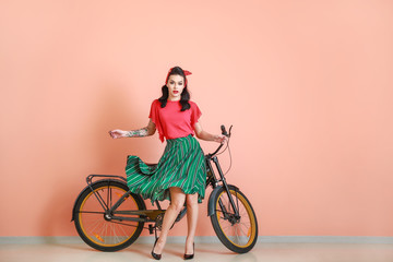 Portrait of beautiful tattooed pin-up woman with bicycle near color wall