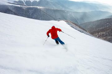 Fototapete - A skier is riding off piste.