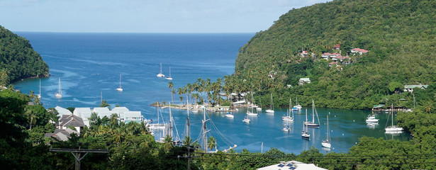 Marigot Bay marina with boats and yachts surrounded by lush green jungle forest landscape on Saint Lucia Island in the Caribbean.