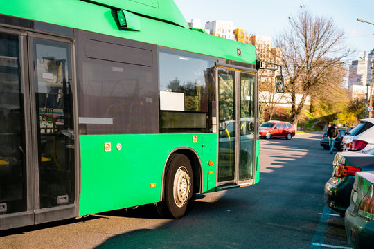 Green electric bus moves along the city's street near the parked cars. Zero emission. Public transport. Urban. E-bus. Ecology