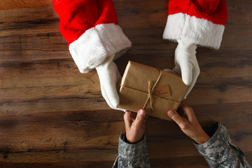 Santa Claus handing a plain wrapped Christmas Present to a soldier. High angle shot with only hands...
