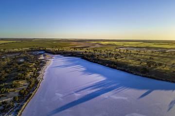 Sunset casting long tree shadows on salt Lake Hardy. Murray-Sunset National Park, Victoria, Australia
