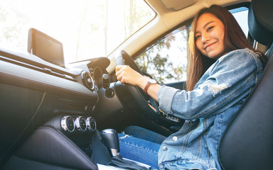 Closeup image of a woman holding steering wheel while driving a car