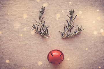 Minimal reindeer made from rosemary and red decor bell, Christmas hipster festive background