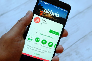 BANDAR SERI BEGAWAN,BRUNEI - JULY 25TH,2018 : A male hand holding smartphone with airbnb app on an android Google Play Store