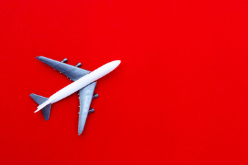 Poster Airplane airplane stand on red paper background. modern plane isolated on red backdrop. travel and transportation idea.