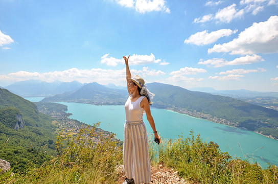 A young happy woman wearing a hat admires a panoramic view on the Lake Annecy from mont Veyrier to mont Baron hiking track, France