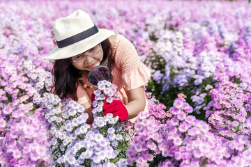 Scientist girl wear red gloves, hold magnifying glass for observing Margaret flower and White cutter flower in garden. . Wall mural