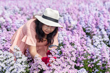 Scientist girl wear red gloves, hold magnifying glass for observing Margaret flower and White cutter flower in garden. Wall mural