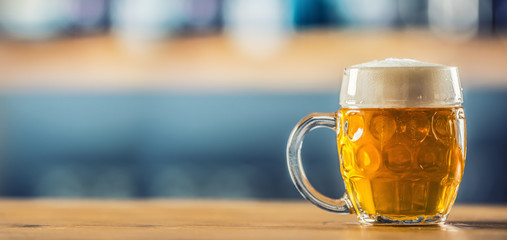 Mug of cold beer on bar counter in pub or restaurant