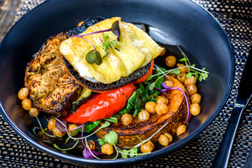 A dish of vegetables, Halloumi, Pumpkin, Bell Pepper and Eggplant stacked up on a dark blue plate.