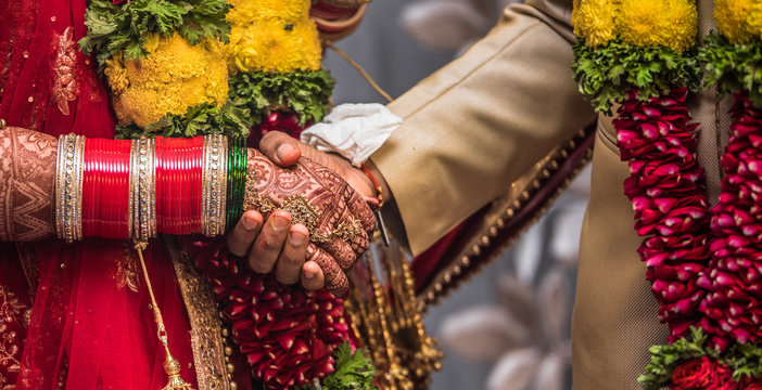 Indian Hindu couple wearing traditional Indian dress and floral garland, holding each other hands during their marriage promising blissful life. Beautiful Henna Mehndi art and bangles on birde hands