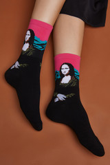 Cropped shot of a girl's foots, lying on a brown background. It is black artwork socks with Mona Lisa print on foots.