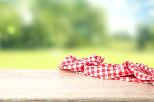 Red checkered picnic cloth on wooden table empty space background.