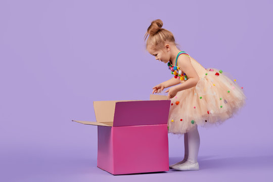 A funny little girl child in a magnificent holiday dress look inside a large gift colored box, on a purple isolated background. Birthday surprise