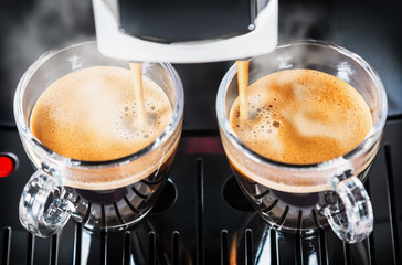 two cups of freshly brewed coffee in the coffee machine
