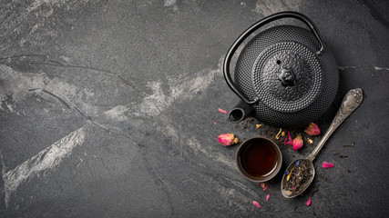 Black japanese cast iron teapot and flower tea with rose buds