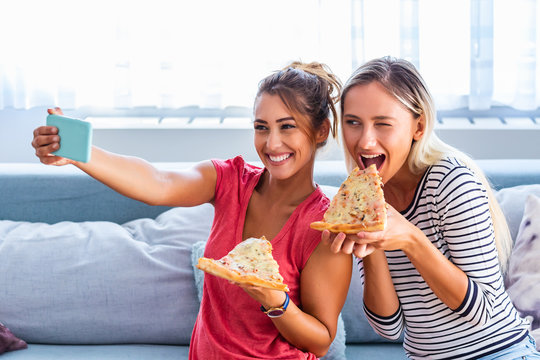 Friends eating pizza and smiling for selfie. They are sharing pizza and making selfie photo on mobile smart phone. They are having party at home, eating pizza and having fun.