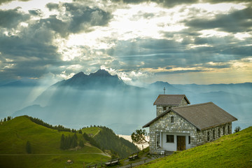 Small chapel with beautiful Mount Pilatus and Lake Lucerne in background as seen from Mount Rigi peak