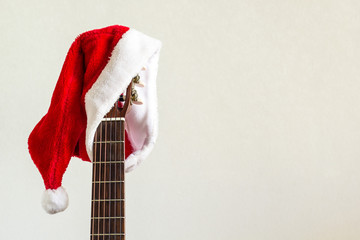 acoustic guitar with red Santa hat. Christmas song music concept on white background