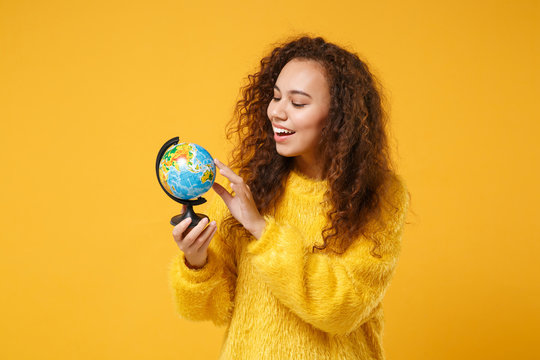 Smiling young african american girl in fur sweater posing isolated on yellow orange wall background studio portrait. People sincere emotions lifestyle concept. Mock up copy space. Holding world globe.