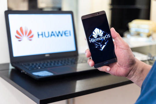 KUALA LUMPUR, MALAYSIA, August, 11, 2019: Huawei officially announced its new operating system, HarmonyOS. Illustrative of developer developing HarmonyOS on computer and smartphone screen.