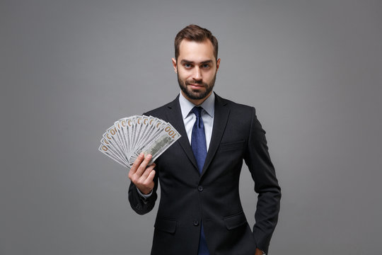 Confident young business man in classic suit shirt tie posing isolated on grey background. Achievement career wealth business concept. Mock up copy space. Hold fan of cash money in dollar banknotes.