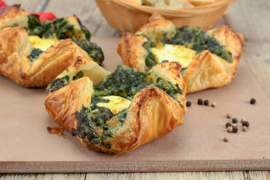 puff pastry with goat cheese and spinach on a chopping board