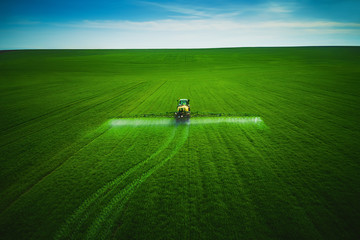 Aerial view of farming tractor plowing and spraying on field Fotomurales