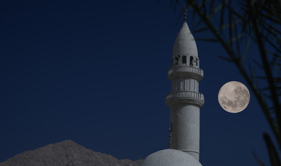 Minaret of a mosque in Jordan with dark blue evening sky and a full moon in the background. Elements of this image furnished by NASA