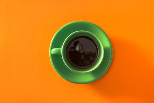 Green cup of coffee on orange background